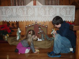 Children placing baby Jesus in the Creche